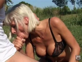 Blonde mature licking and swallowing cock in public