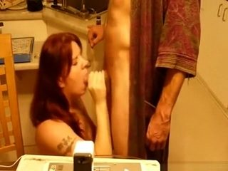 Mature brunette sucks her man's cock in the living room and swallows