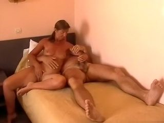 Ponytailed milf gives her man a blowjob and handjob on the bed
